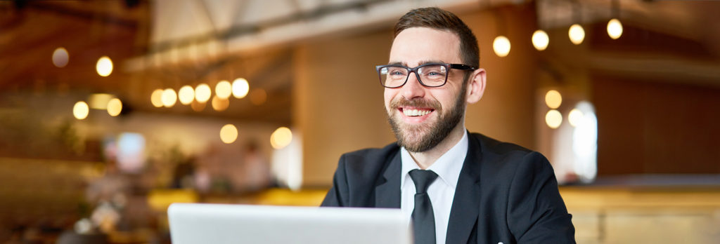 Posh businessman in elegant suit sitting in front of laptop and searching in the net